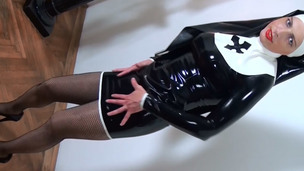 Perverted sweetheart in latex nun suit posing seductively